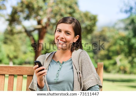 Young woman phoning on the bench