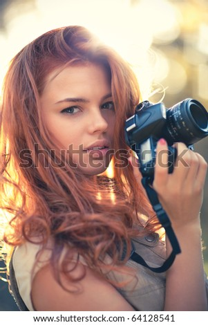Young woman photographer. Soft colors and shallow doff. - stock photo