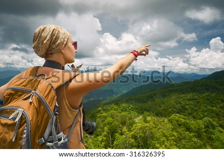 Young woman photographer with backpack with backpack standing on top of the mountain and enjoying valley view with raised hand. Travel to Asia, happiness emotion, summer holiday concept - stock photo