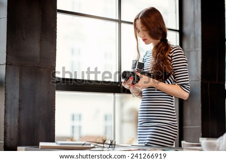 Young woman photographer with old 6x6 frame camera standing near the big window in the cafe