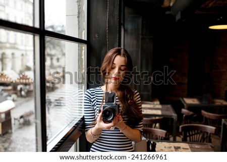 Young woman photographer with old 6x6 frame camera standing near the big window in the cafe - stock photo