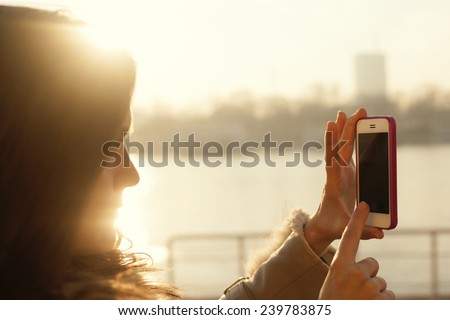 Young woman photographing scenery with mobile phone with sun flare - stock photo