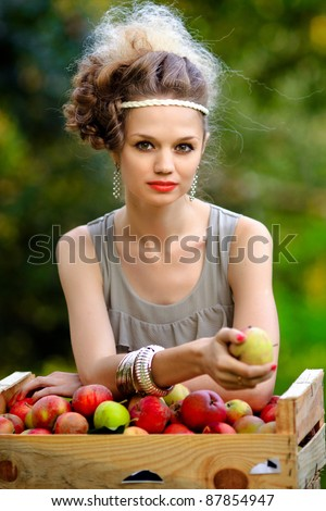 Young woman picking apples from an apple tree - stock photo