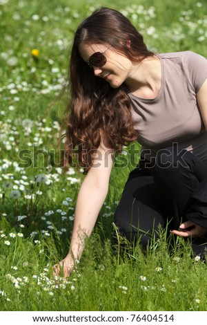 Young woman picking flowers on spring field - stock photo