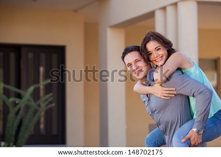 Young woman piggyback riding her husband in front of their new home and smiling - stock photo