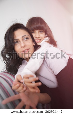 Young woman piggybacking her joyful little daughter at home in white lit room against the window. Smooth morning light, casual style - concept of happy family living and lifestyle - stock photo