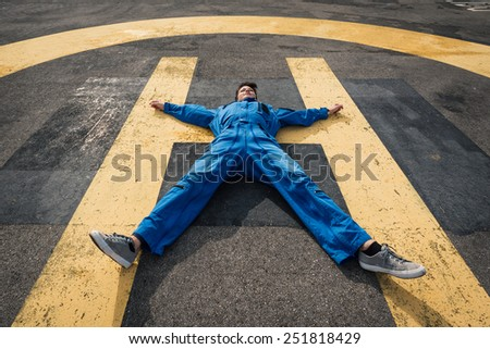 Young woman pilot laying down on helicopter runway. - stock photo