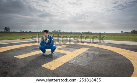 Young woman pilot portrait on helicopter runway. - stock photo