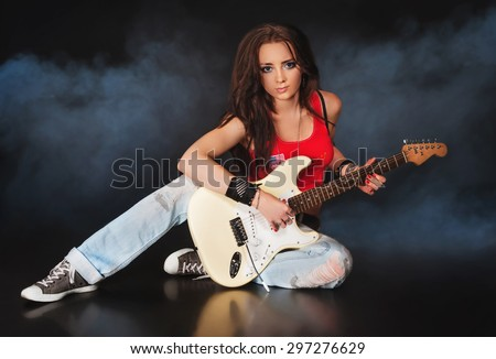 young woman play electric guitar in smoke and black background - stock photo