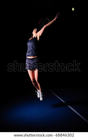 young woman play tennis on blue court - stock photo