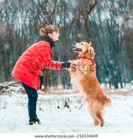 young woman play with her dog golden retriever on the snow - stock photo