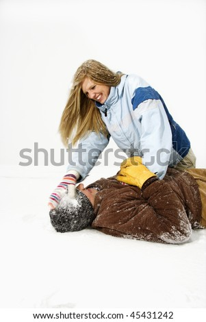 Young woman playfully sits atop a young man and hits his head with a snowball. Vertical shot. - stock photo