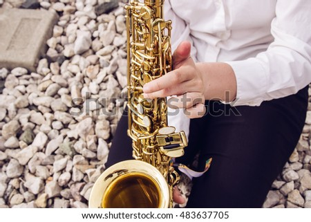 Young woman playing a saxophone. Outdoors, railway road.