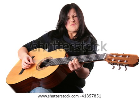 Young woman playing an acoustic guitar - stock photo