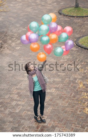 Young woman playing and holding balloons at park in Taipei, Taiwan, Asia. - stock photo