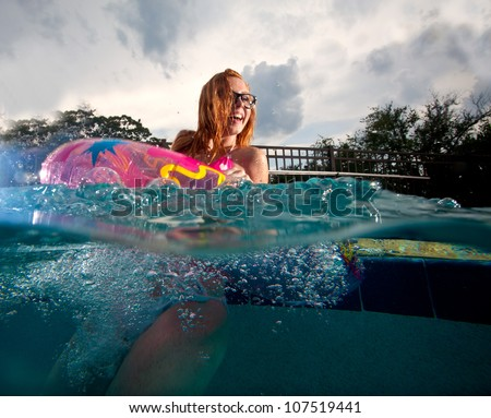 Young Woman playing and swimming in a Pool - stock photo