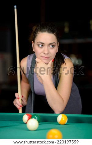 Young woman playing billiards in the dark billiard club - stock photo