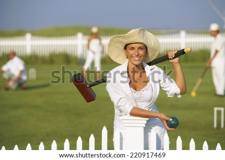Young woman playing croquet - stock photo