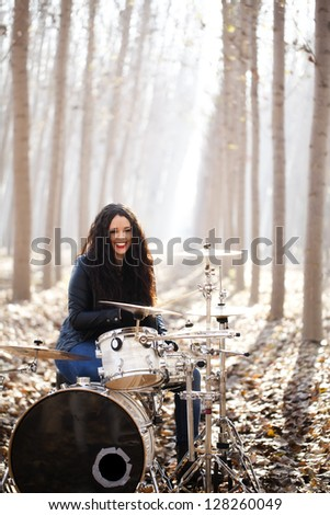 Young woman playing drums outdoors. - stock photo