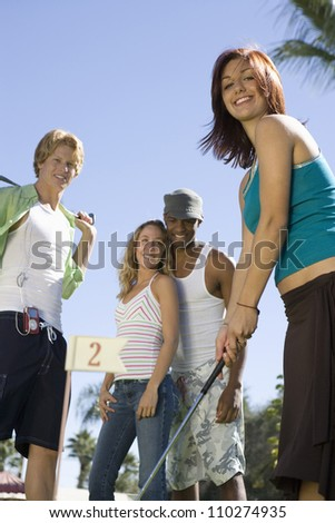 Young woman playing golf with friends