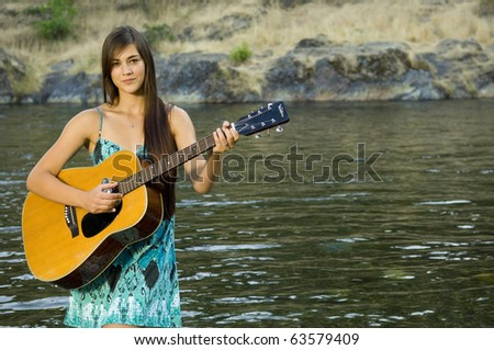 Young woman playing guitar by river in summer