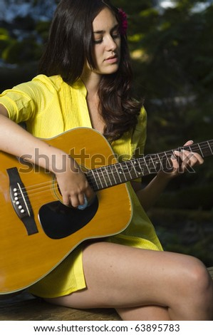 Young woman playing guitar by waterfall in summer - stock photo