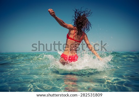 Young woman playing in the sea. Summer vacation concept - stock photo
