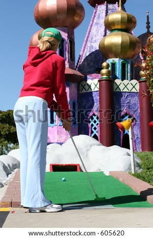 Young woman playing miniature golf - stock photo