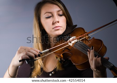 Young woman playing music by violin