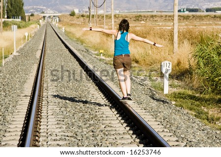 Young woman playing on a railway track. - stock photo
