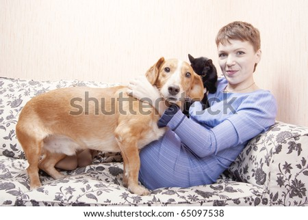 Young woman playing on a sofa with a little dog - stock photo