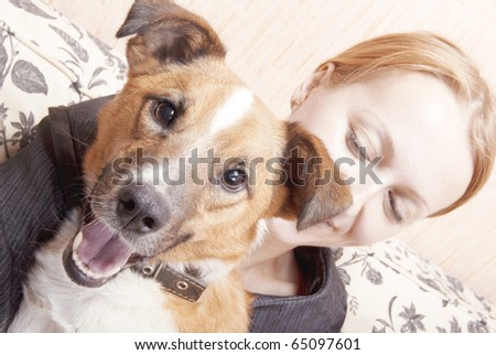 Young woman playing on a sofa with a little dog