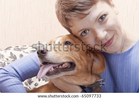 Young woman playing on a sofa with her joyful dog
