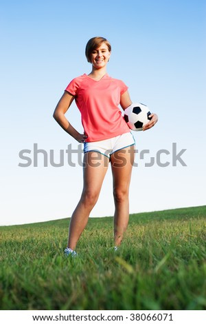 Young woman playing soccer in a field, from a complete series of photos.