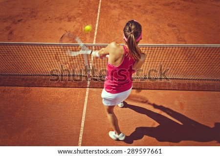 Young woman playing tennis.High angle view.Backhand volley. - stock photo