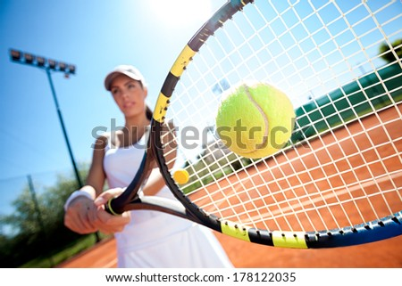young woman playing tennis on a sunny day - stock photo