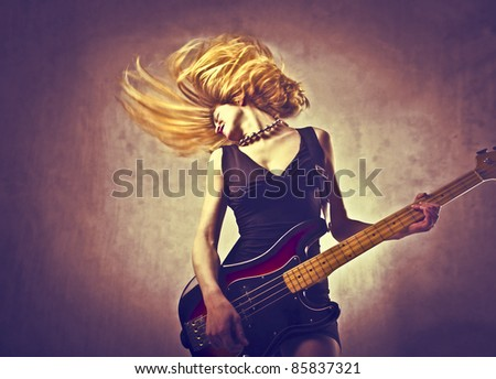 Young woman playing the guitar - stock photo