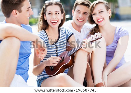Young woman playing ukulele friends - stock photo
