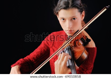 Young woman playing violin. Isolated on the black background