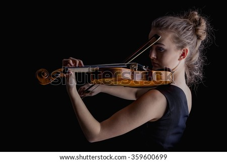 Young woman playing violin on black background  - stock photo