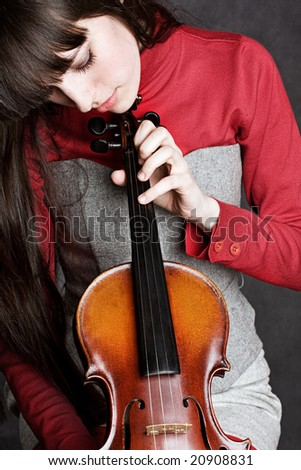 young woman playing violin over gray background. - stock photo