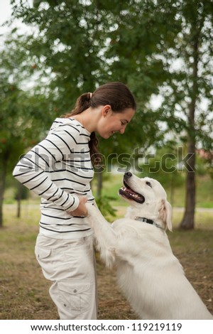 Young woman playing with a dog - stock photo