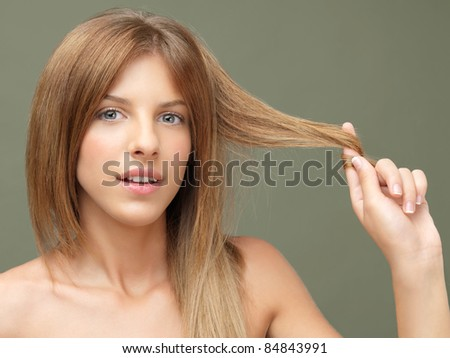 young woman playing with a hair strand - stock photo