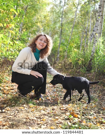 Young woman playing with black labrador retriever puppy in the autumn forest - stock photo