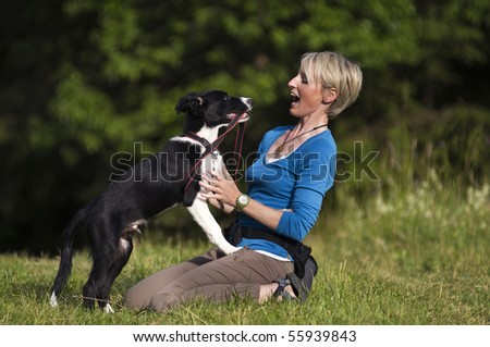 Young woman playing with border collie dog outdoor - stock photo