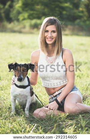 Young woman playing with cute terrier dog outdoors in the park. - stock photo
