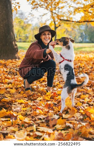Young woman playing with dog outdoors in autumn - stock photo