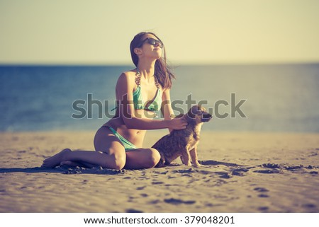 Young woman playing with dog pet on beach during sunrise or sunset.Hipster girl and dog having fun on seaside.Cute neglected stay dog adopted by caring young woman.Puppy and his owner enjoying sunset - stock photo