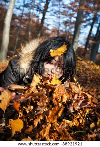 Young woman playing with fallen autumn leaves