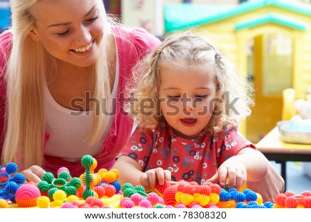 Young woman playing with girl - stock photo